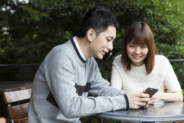 Young couple watching smartphone on cafe terrace