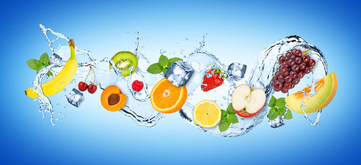 water splash panorama with various fruits ice cubes and fresh peppermint leafs  on blue white...