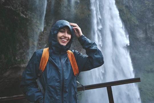 Girl in waterproof clothing stands under the Seljalandsfoss waterfall in Iceland. woman with small orange backpack