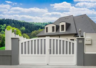 Modernes PVC-Gartentor in grau und weiß und Einfamilienhaus in schöner Landschaft - Modern PVC garden door and family home in beautiful landscape