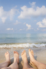 Two people legs on sea beach. Blue sky with clouds