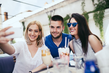 Group of young and attractive three people enjoying private party and making selfie photo. Swimming pool in background. Man with two beautiful women.