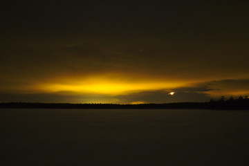 Light pollution in wilderness. Yellow glow over lake and forest.