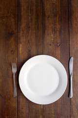White plate on wooden background, copy space