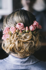 wedding preparations. Young beautiful bride getting her hairstyle, braiding roses in hair