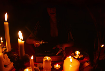 A witch carrying out a ritual with magic book and candles. Halloween concept, black magic ritual.