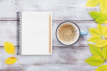 Open notebook and morning cup of coffee on rustic wooden table top view. Cozy autumn breakfast. Fall bucket list. Flat lay style.