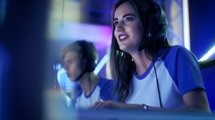 Beautiful Professional Gamer Girl and Her Team Participate in eSport Cyber Games Tournament. She Has Her Headphones and as a Team Leader She Commands Strategical Maneuvers into Microphone.