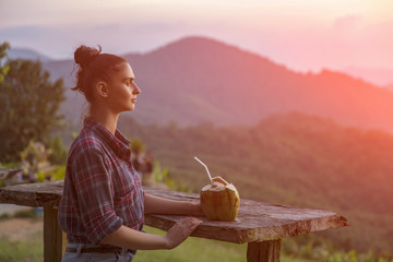 Hipster young girl with coconut enjoying sunset on peak mountain. Tourist traveler on background valley landscape view mockup.