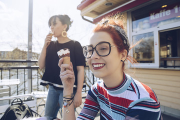 Hipster female friends eating ice cream by shop