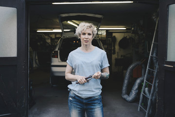 Portrait of female owner holding work tool while standing at entrance of auto repair shop