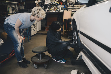 Customer looking at female mechanic examining car tire at auto repair shop
