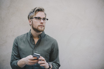 Thoughtful male computer programmer holding smart phone against beige wall in office