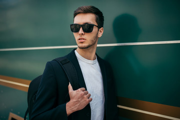 Stylish fashion young Caucasian man in sunglasses and black jacket with backpack walking over green city background. Fashionable business tourist travel around the world for new project and clients.