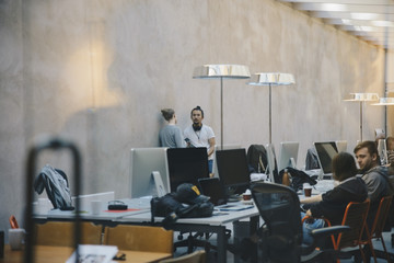 Male and female computer programmers discussing in creative office