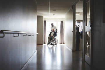 Full length of male nurse pushing senior man on wheelchair at hospital corridor