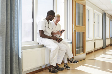 Full length of male and female nurses using smart phone while sitting on window sill at hospital corridor