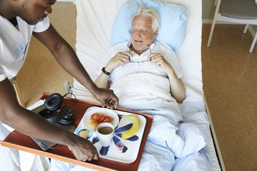 High angle view of male nurse serving breakfast to senior man in hospital ward