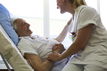 Side view of happy senior man talking to female nurse on hospital bed