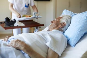 Senior man looking at female nurse serving breakfast while lying on hospital bed