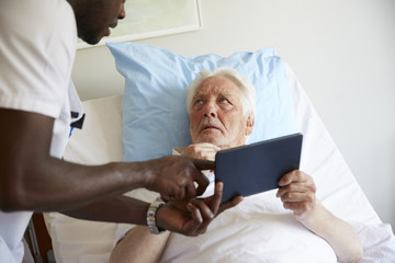 Senior man looking at male nurse while using digital tablet on bed in hospital ward