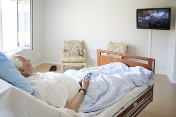 Senior man watching TV while reclining on bed in hospital ward