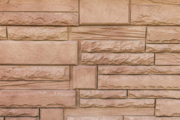 Stone wall brick texture background beige surface facade. Plstic simulation siding panel.