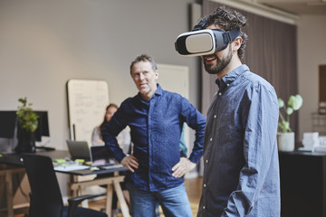 Businessman looking at colleague using virtual reality simulator in office