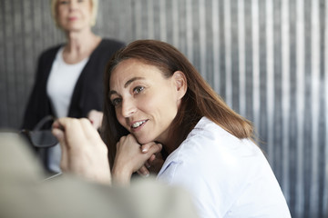 Mature female professional sitting with colleagues in board room during meeting