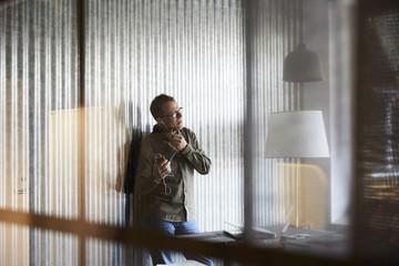 Mature businessman talking on smart phone through headphones seen from glass