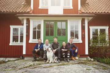 Portrait of family sitting with Australian Shepherd at entrance of house