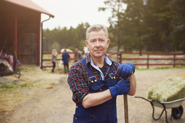Portrait of confident farmer holding pitchfork while standing in farm