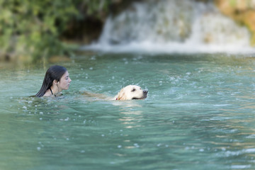 Teenager bathing in a lake with her dog.