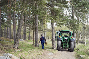 Rear view of farmer walking by tractor amidst trees on field