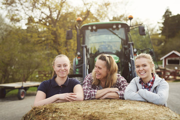 Smiling mother and daughters leaning on hay bale