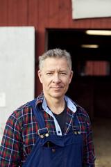Portrait of confident farmer standing against barn