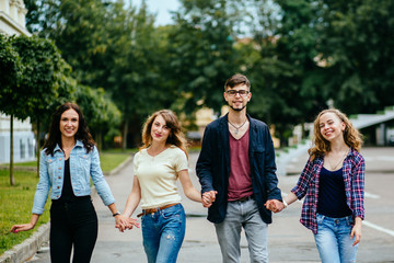 Group of Four Teenagers Holding By Hands And Wakking at Park, Italy