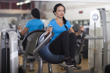 Bodybuilding. woman exercising in gym abs legs up.