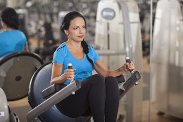 Bodybuilding. woman exercising in gym with exercise-machine