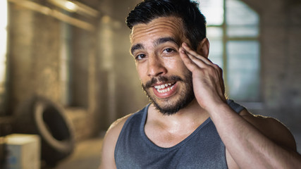 Muscular Man Wipers Sweat of His Forehead after Intensive Cross Fitness Bodybuilding Training. He Smiles Charmingly. He Wears Sleeveless Shirt and Works out in a Gym.