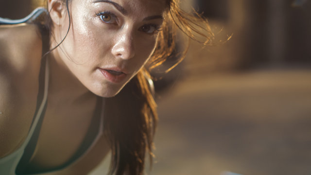 Close-up Shot of a Beautiful Athletic Woman Looks into Camera. She's Tired after Intensive Cross Fitness Exercise.