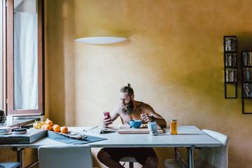 young bearded man indoor having breakfast using smartphone