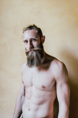 waist up young bearded man bare chested looking camera