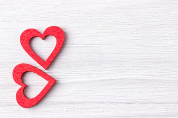 Two red hearts on a white wooden background. Top view. Free space