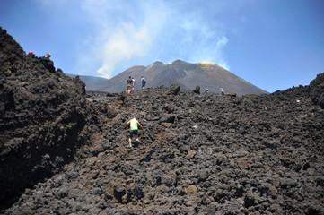 Mühsamer Aufstieg eines kleinen Jungen über ein frisches Lavafeld zum rauchenden Gipfel des Vulkans Ätna, Sizilien/Italien