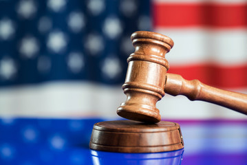 Law and justice symbols on American flag background.