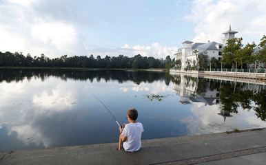 A young boy fishes ahead of the arrival of Hurricane Irma at Lakeside Park, in front of the Bohemian Hotel in downtown Celebration