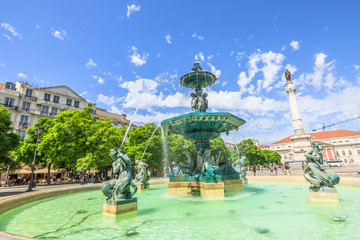One of two baroque fountains in Praca Dom Pedro IV or Rossio Square in Lisbon downtown, Portugal, Europe. The National Theater D. Maria II and statue of Dom Pedro IV on background. Sunny day.