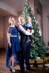 Family, father mother and son near Christmas tree. Eve