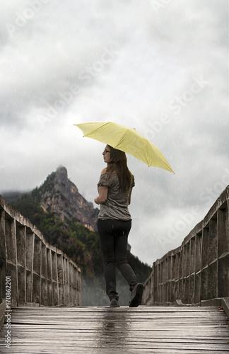 woman standing in the rain on the bridge fotolia com の ストック写真
